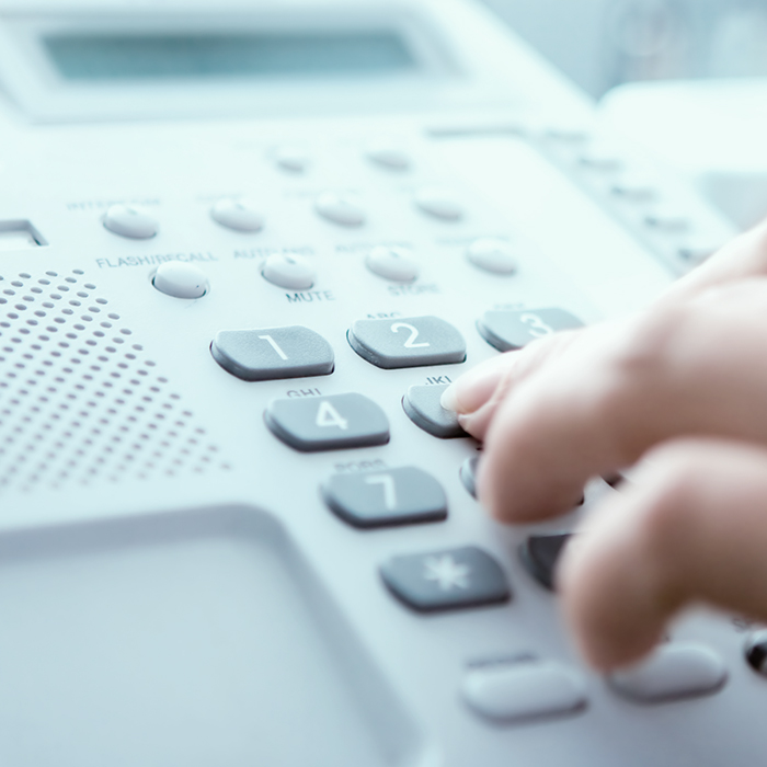Photo of someone dialing a phone